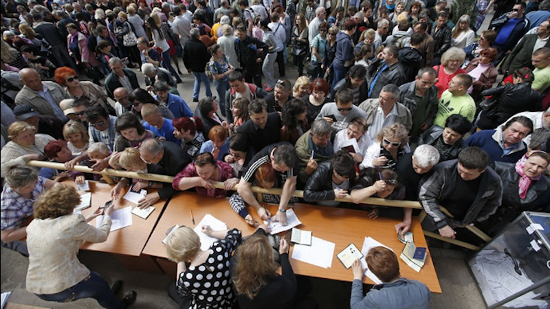 People stand in a line to receive ballots from members of a local election commission during the referendum on the status of Donetsk region in the eastern Ukrainian city of Mariupol